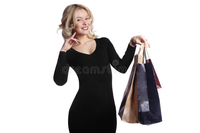 Mujer joven que hace compras que sostiene bolsos aislados en el fondo blanco Moda y ventas Comprador con los bolsos y los regalos fotos de archivo libres de regalías