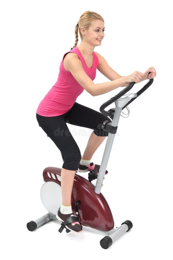 Mujer joven que hace ejercicio biking de interior fotografía de archivo