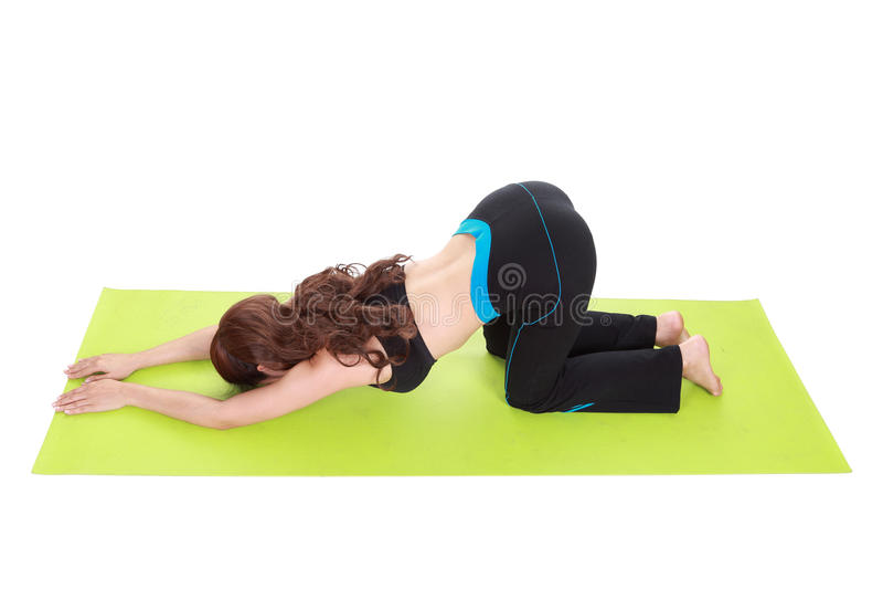 Mujer joven que hace ejercicio de la yoga con la estera de la yoga foto de archivo
