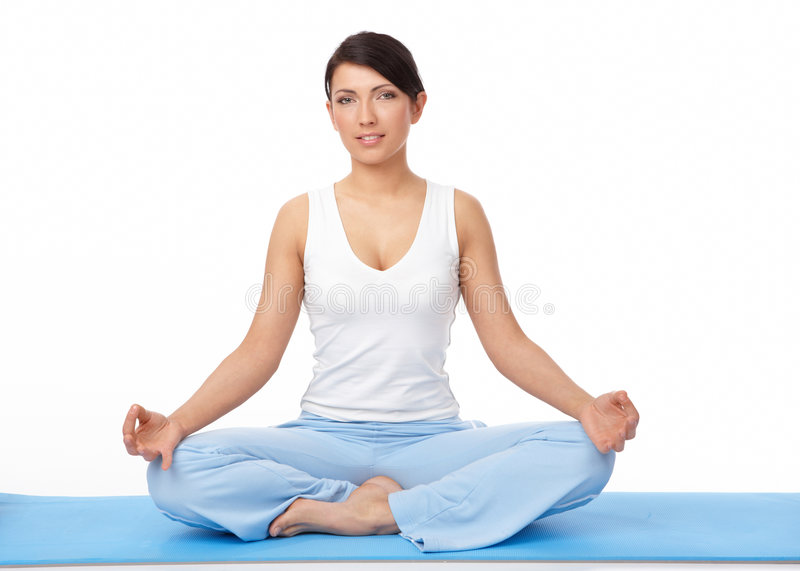 Mujer joven que hace ejercicio de la yoga en la estera azul imagenes de archivo