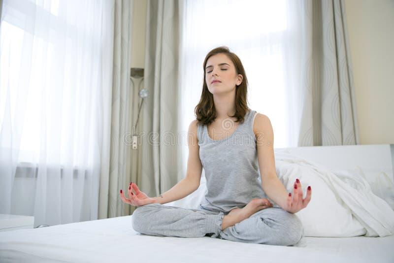 Mujer joven que hace ejercicios de la yoga imágenes de archivo libres de regalías