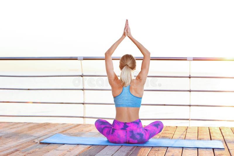 Mujer joven que hace ejercicios de la yoga en el embarcadero fotografía de archivo libre de regalías