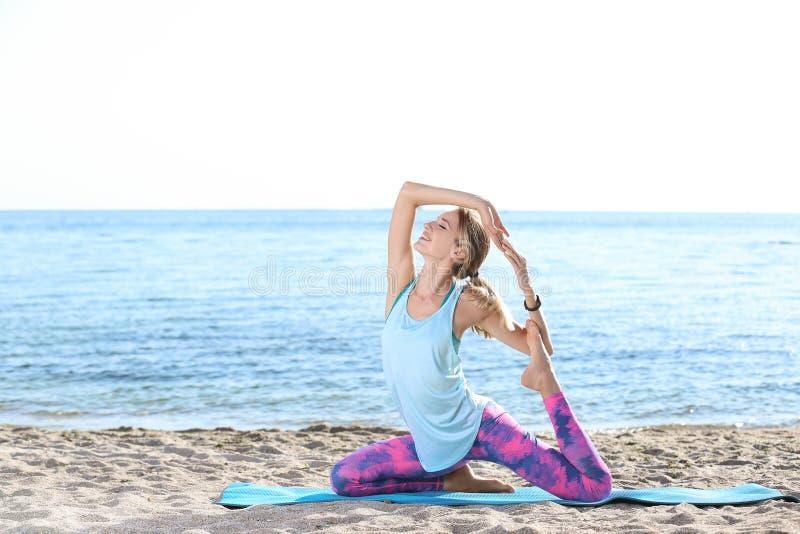 Mujer joven que hace ejercicios de la yoga en la playa fotografía de archivo libre de regalías