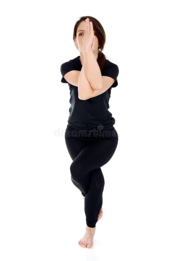 Mujer joven que hace el asana Garudasana Eagle Pose de la yoga foto de archivo libre de regalías