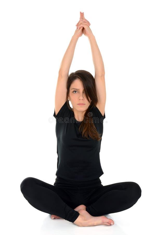 Mujer joven que hace el asana Lotus Pose With Hands Up de la yoga imagen de archivo