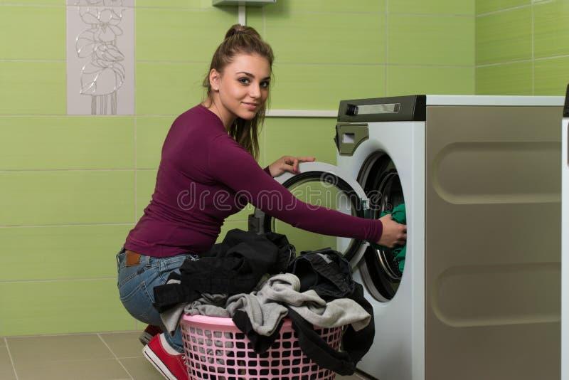 Mujer joven que hace el lavadero del quehacer doméstico imagen de archivo libre de regalías