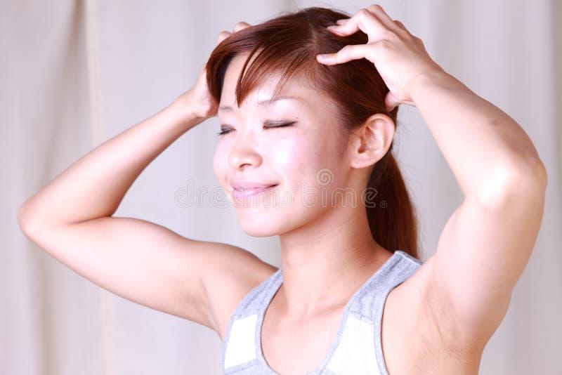 Mujer joven que hace el masaje principal del uno mismo fotografía de archivo libre de regalías