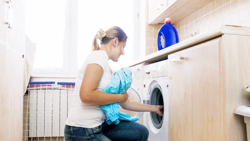 Mujer joven que hace el quehacer doméstico en lavadero imagenes de archivo