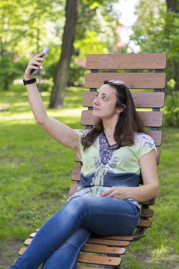 Mujer joven que hace el selfie en el parque Mujer joven atractiva con el pelo rubio largo que hace el selfie el d?a de verano en  fotos de archivo libres de regalías
