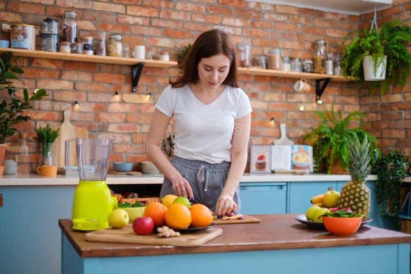 Mujer joven que hace el smoothie en cocina imagen de archivo libre de regalías