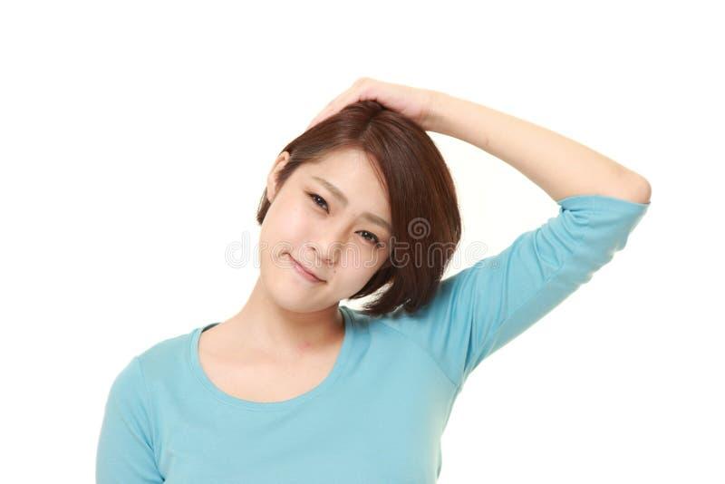 Mujer joven que hace estiramiento del cuello imagen de archivo