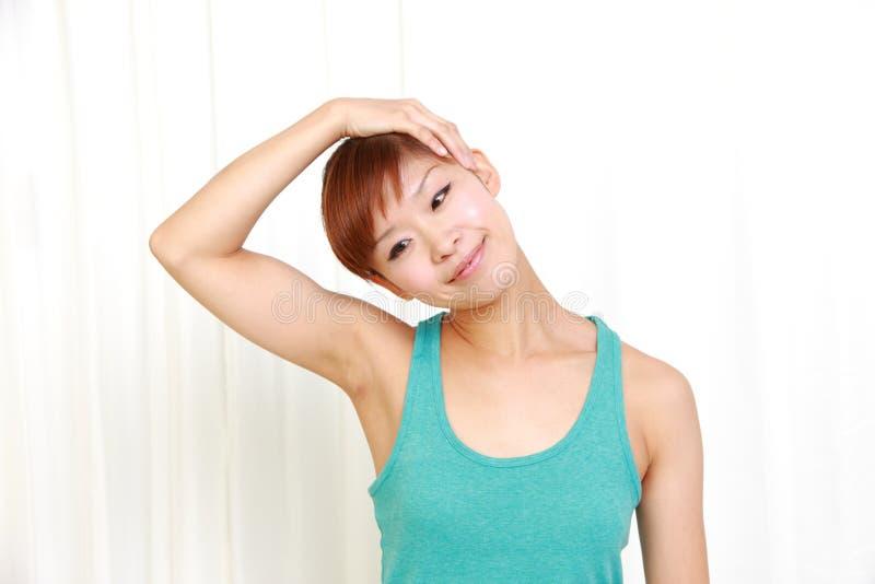 Mujer joven que hace estiramiento del cuello del uno mismo fotografía de archivo