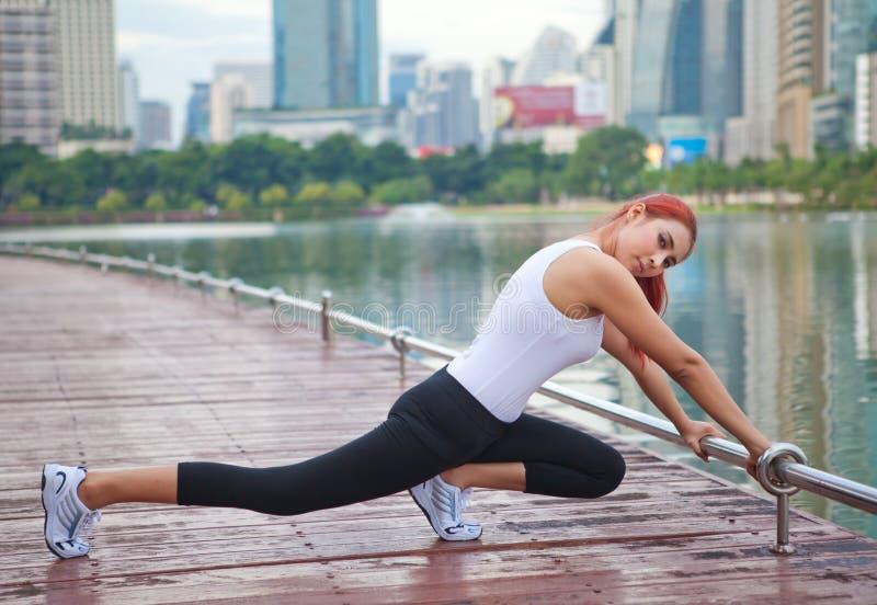 Mujer joven que hace estirando ejercicio imagenes de archivo