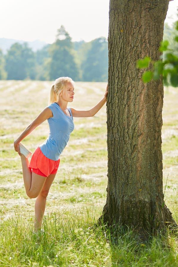Mujer joven que hace estirar ejercicio imagen de archivo