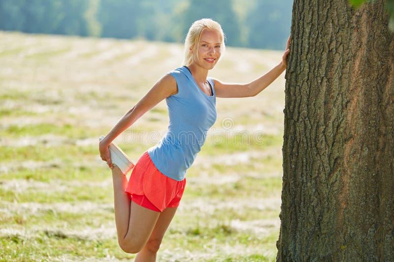 Mujer joven que hace estirar ejercicios fotografía de archivo libre de regalías