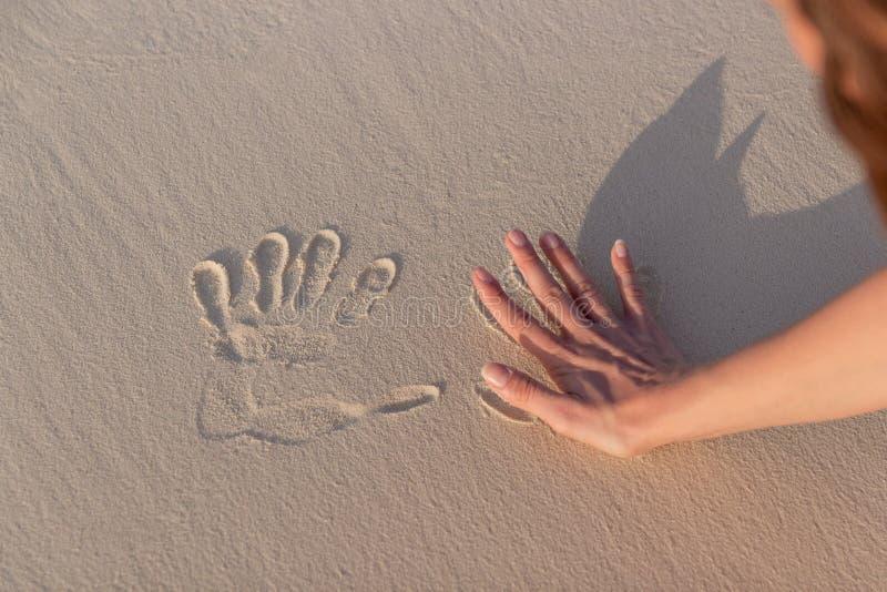 Mujer joven que hace Handprints en la arena blanca imagenes de archivo