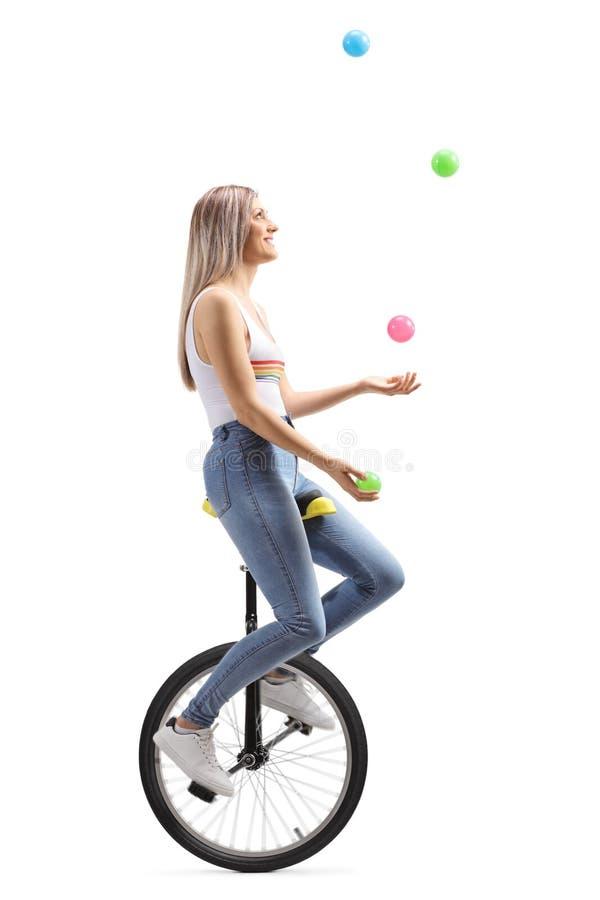 Mujer joven que hace juegos malabares con las bolas en un unicycle fotografía de archivo