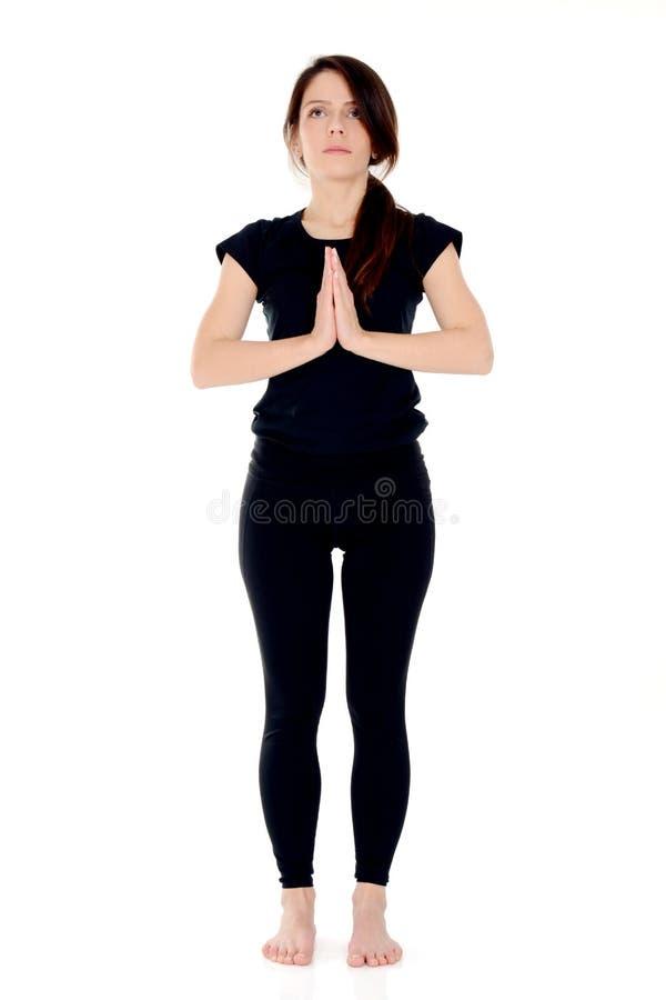 Mujer joven que hace la actitud de Namaste de la yoga, posición delantera foto de archivo