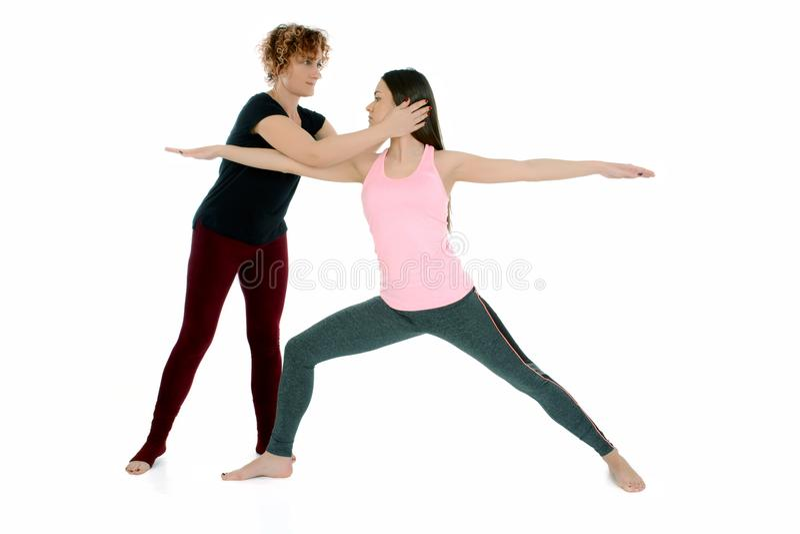 Mujer joven que hace la actitud Virabradasana del guerrero del asana de la yoga imágenes de archivo libres de regalías