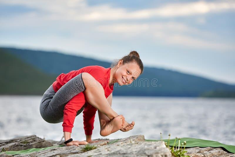 Mujer joven que hace la balanza del brazo de la actitud de la yoga en el río grande cercano de piedra imagen de archivo libre de regalías