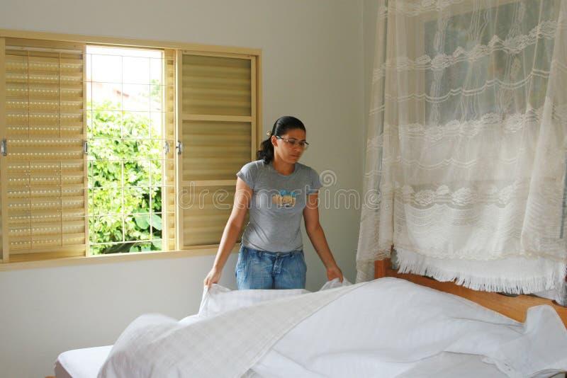 Mujer joven que hace la cama fotografía de archivo