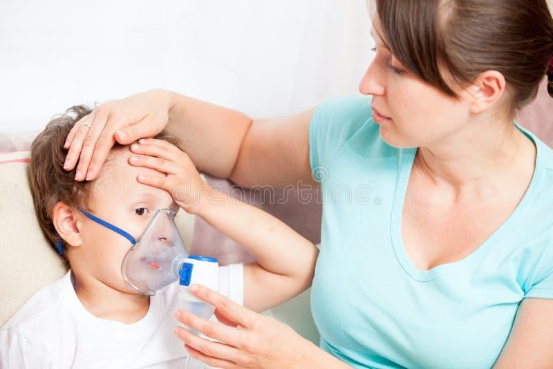 Mujer joven que hace la inhalaci?n con un hijo del nebulizador fotos de archivo
