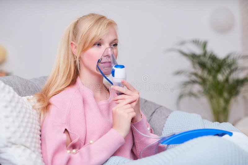 Mujer joven que hace la inhalaci?n con un nebulizador en casa imagen de archivo libre de regalías