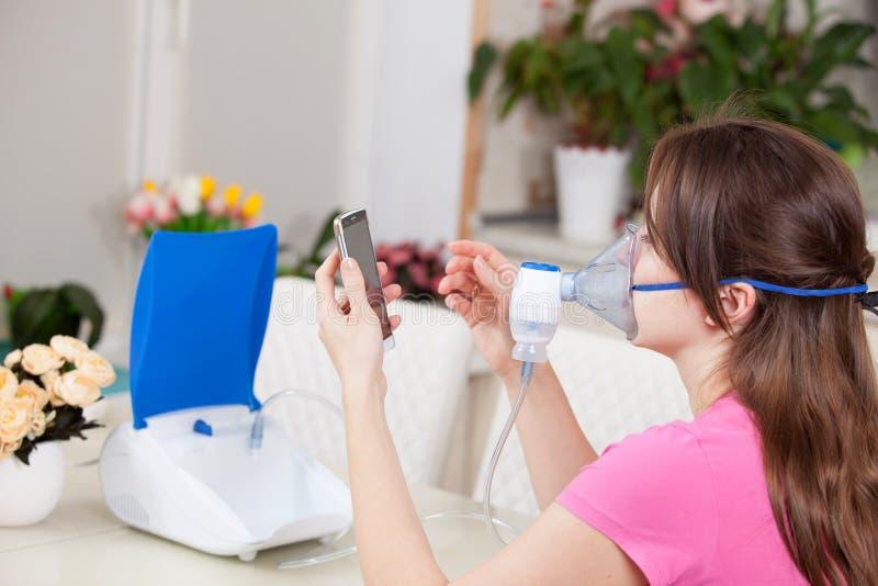 Mujer joven que hace la inhalaci?n con un nebulizador en casa marca el n?mero del doctor para una consulta imagen de archivo