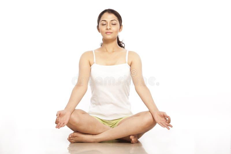 Mujer joven que hace la meditación foto de archivo