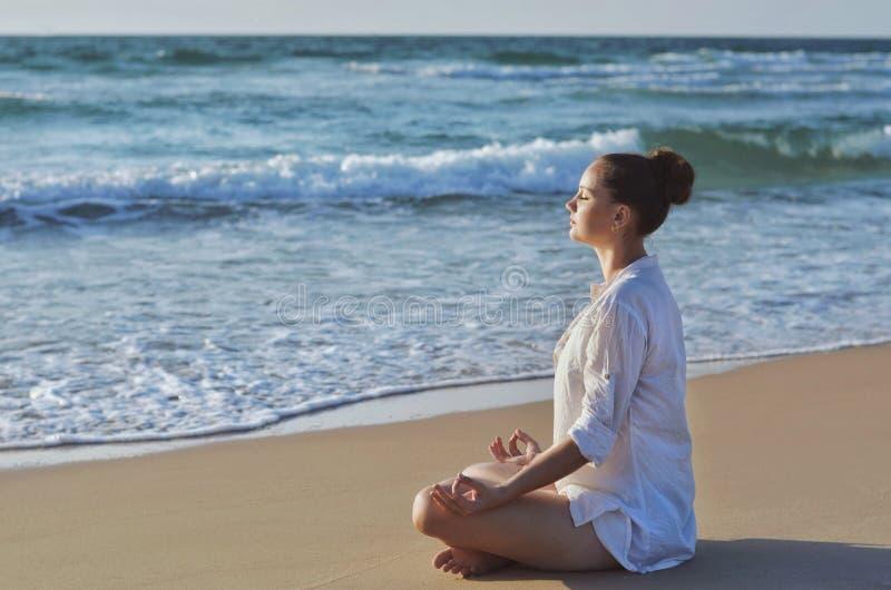 Mujer joven que hace la meditación en la playa cerca del mar imagen de archivo libre de regalías
