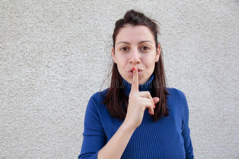 Mujer joven que hace la muestra del silencio imagenes de archivo