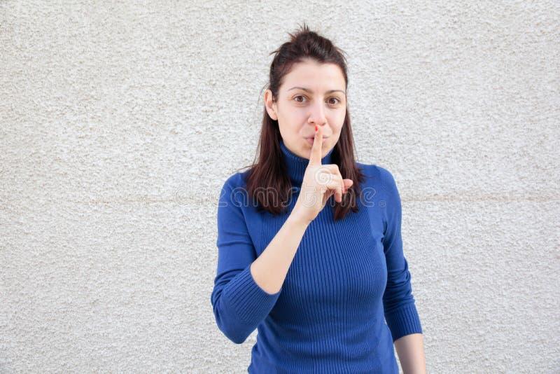 Mujer joven que hace la muestra del silencio fotografía de archivo