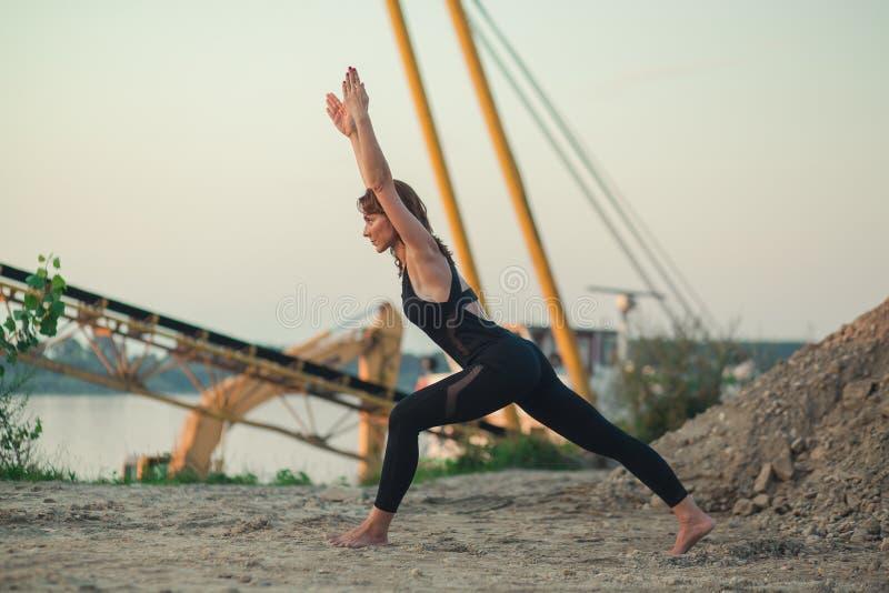 mujer joven que hace la variación de la alta actitud de la yoga de la estocada fotos de archivo