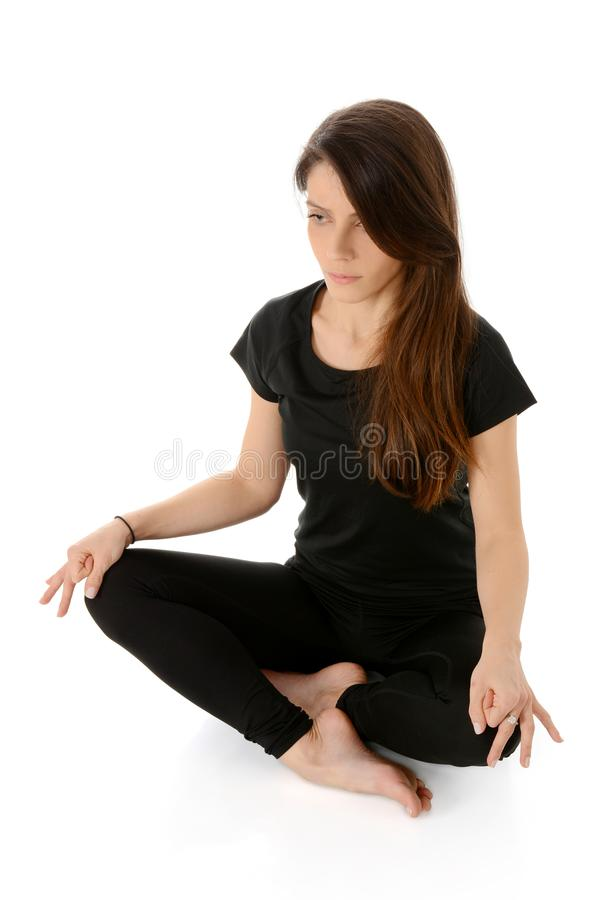 Mujer joven que hace la yoga, actitud fácil de la sentada de Sukhasana imagen de archivo