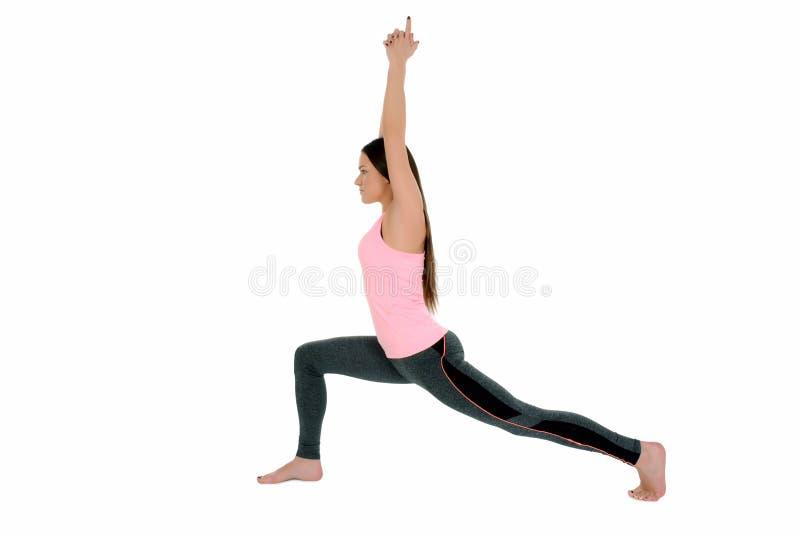 Mujer joven que hace la yoga, actitud Virabhadrasana del guerrero imagen de archivo libre de regalías