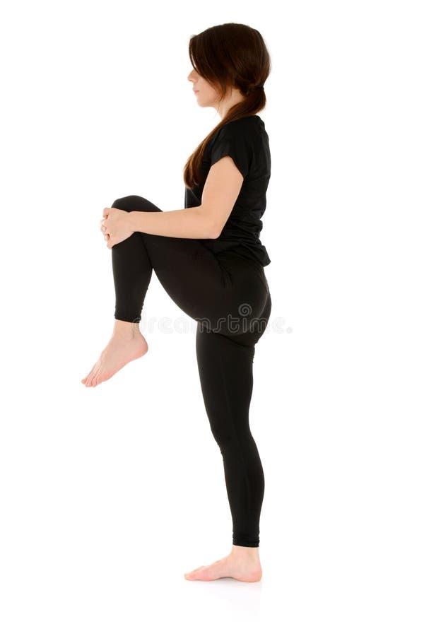 Mujer joven que hace la yoga que se coloca en una pierna fotografía de archivo