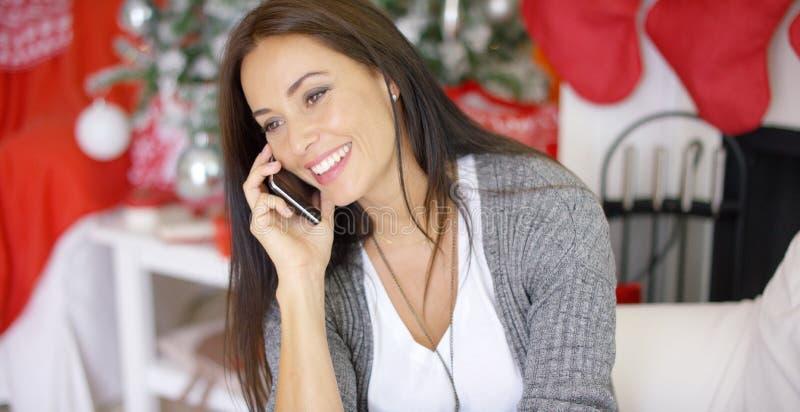 Mujer joven que hace llamadas de la Navidad a los amigos imagen de archivo libre de regalías