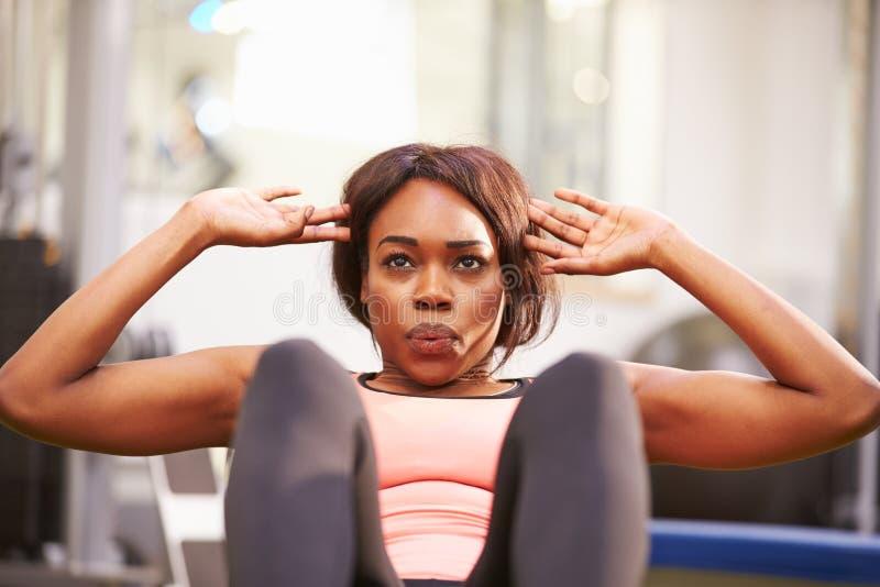 Mujer joven que hace los crujidos en un gimnasio, cierre para arriba fotografía de archivo libre de regalías