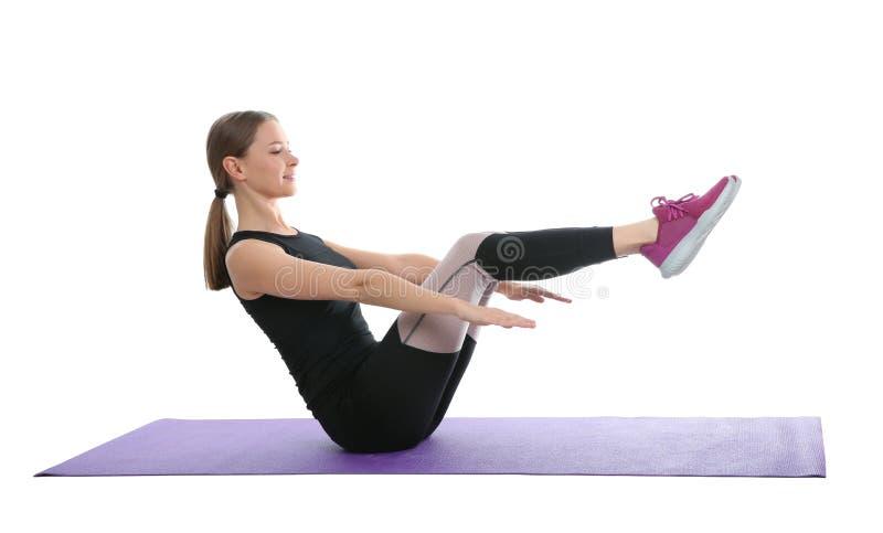 Mujer joven que hace los ejercicios de los deportes aislados en blanco foto de archivo libre de regalías