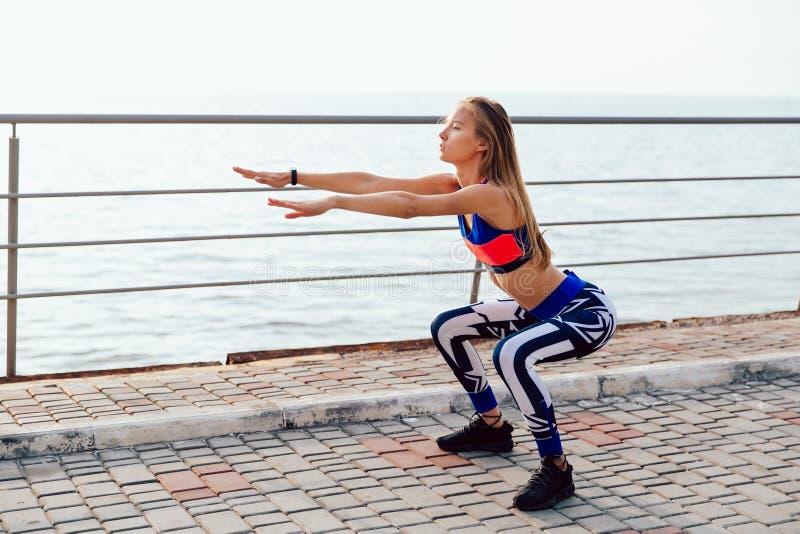 Mujer joven que hace posiciones en cuclillas al aire libre fotos de archivo libres de regalías