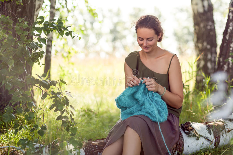 Mujer joven que hace punto en bosque imagenes de archivo