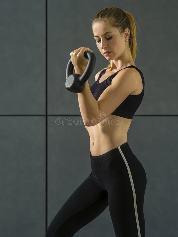 Mujer joven que hace rizos del bíceps con el kettlebell fotos de archivo