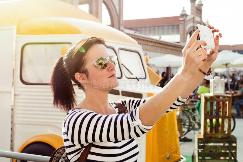 Mujer joven que hace un selfie, al lado del camión de la comida fotografía de archivo