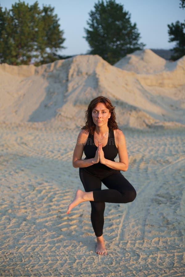 mujer joven que hace una actitud agazapada legged de la yoga al aire libre fotos de archivo libres de regalías