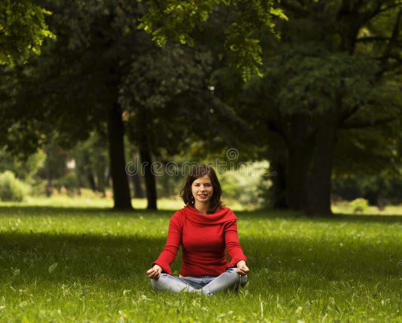 Mujer joven que hace yoga foto de archivo