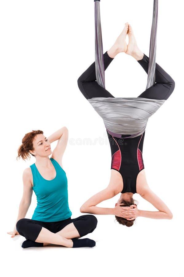 Mujer joven que hace yoga aérea con el instructor foto de archivo