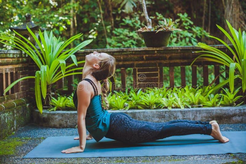 Mujer joven que hace yoga afuera en el ambiente natural imagenes de archivo