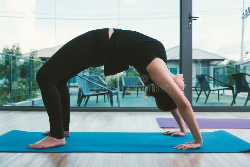 Mujer joven que hace yoga de la actitud del puente foto de archivo libre de regalías