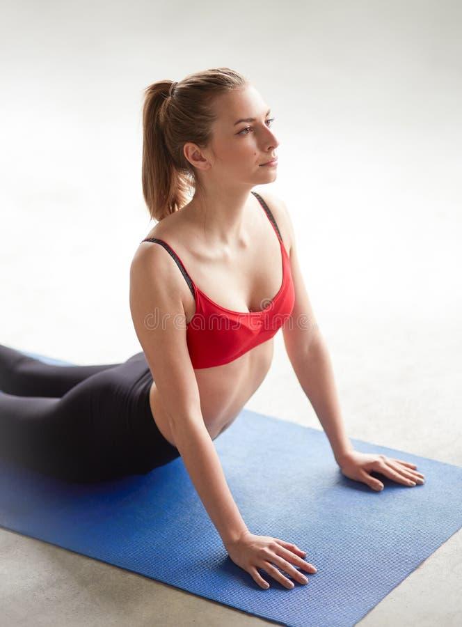 Mujer joven que hace yoga dentro foto de archivo