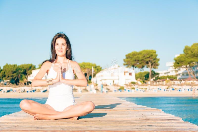 Mujer joven que hace yoga en el embarcadero fotos de archivo